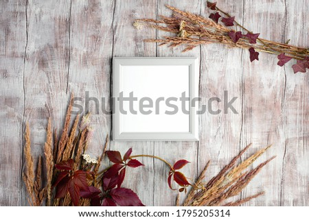Poster frame autumn mockup. Top view,  Stylish minimal composition with photo frame on rustik white wooden background. Holiday concept. Flat lay. Copy space
