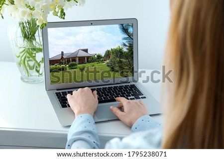 Woman choosing new house online using laptop or real estate agent working at table, closeup Royalty-Free Stock Photo #1795238071