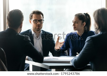 Confident young businessman in eyeglasses holding negotiations meeting with partners in formal wear. Focused diverse employees discussing development strategy or working issues, sitting at table. Royalty-Free Stock Photo #1795243786