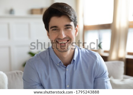 Profile picture of young handsome man sitting on sofa, enjoying talking with friends in social network. Smiling millennial guy job seeker communicating via video call with hr manager from home. Royalty-Free Stock Photo #1795243888