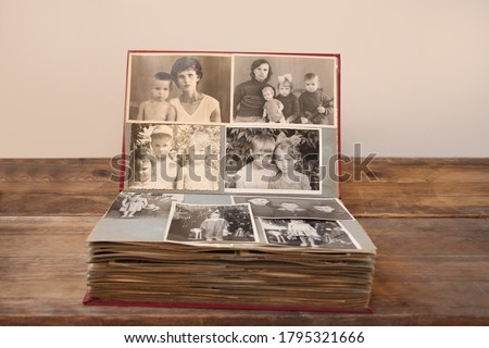 old retro album with vintage monochrome photographs in sepia color, taken in 1955-1960, concept of genealogy, the memory of ancestors, family ties, childhood memories Royalty-Free Stock Photo #1795321666