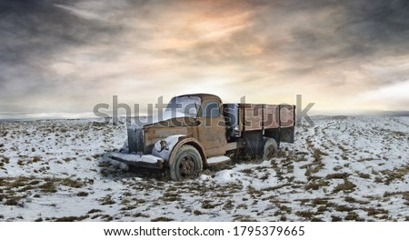A picture of the abandoned truck in the midst of snowy plain