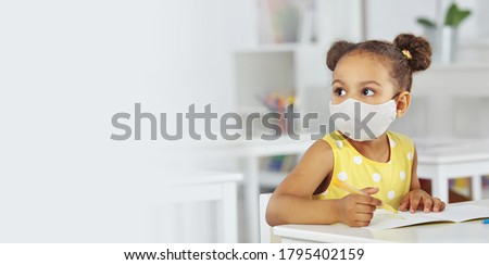 A dark-skinned girl in a medical mask for respiratory protection in a yellow dress listens attentively to the teacher. white background. Banner format #1795402159