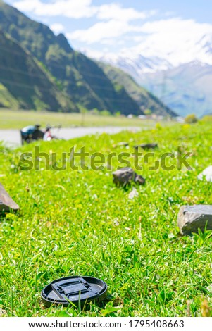 Black camera cap left on the grass in nature. Lost photography accessories on holidays concept. #1795408663