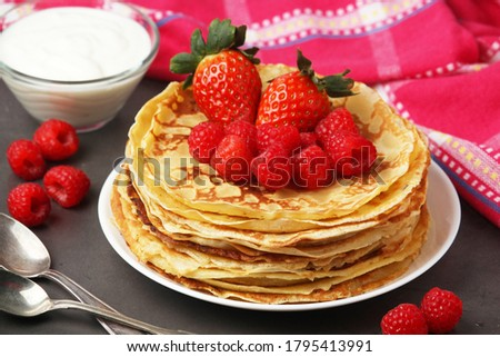 Russian cuisine national dish bliny with fresh berries Royalty-Free Stock Photo #1795413991