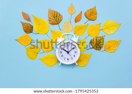 Alarm clock on blue background decorated with colorful fallen leaves. Autumn time concept. Selective focus. Copy space, flat lay #1795425352