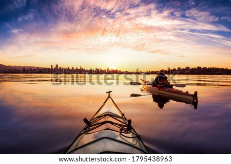Kayakers enjoying the beautiful sunrise. Picture taken near Kitsilano Beach, Vancouver, BC, Canada.