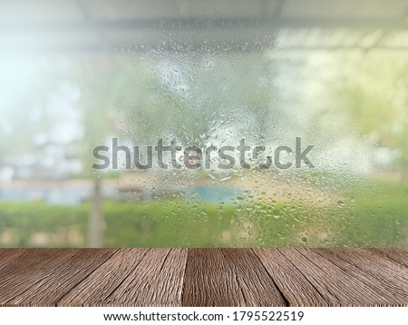 Empty wooden table for displaying products. On a rainy day, seeing a drop of water on the outer glass blurred (Background, rainy day window)