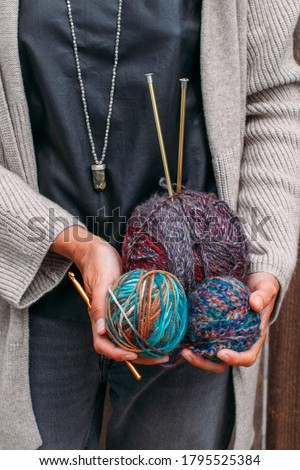 Woman holds multi-colored bright balls of woolen yarn for knitting. Knit yarn, knitting needles, skeins. Beautiful colors for knitting. Handmade creative knitting concept. #1795525384