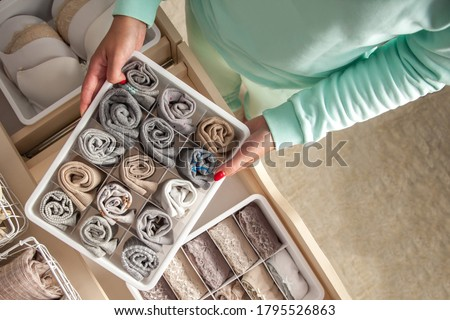 Unidentified neat housewife puts container with socks and pantyhose on wardrobe drawer during general cleaning by modern storage system. Concept of beautiful and comfortable organization Royalty-Free Stock Photo #1795526863