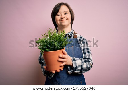 Young down syndrome gardener woman wearing worker apron holding green plant pot with a happy face standing and smiling with a confident smile showing teeth Royalty-Free Stock Photo #1795627846