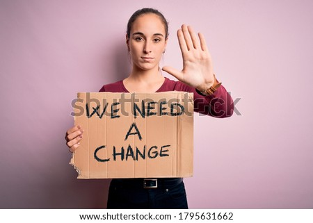 Young beautiful activist woman asking for change protesting holding banner with message with open hand doing stop sign with serious and confident expression, defense gesture