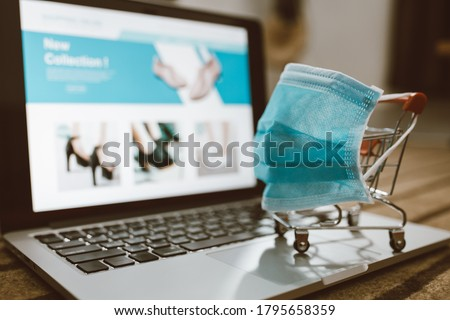 Trolley shopping cart wearing protective mask on a computer laptop keyboard. Concept for shopping online or e-commerce from internet for Coronavirus COVID-19 disease protection. Royalty-Free Stock Photo #1795658359