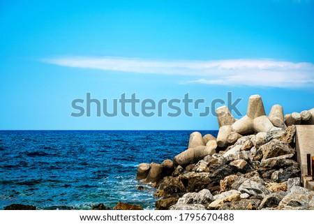 Sea landscape with rocks and concrete tetrapods for coastal protection from breakwaters  Royalty-Free Stock Photo #1795670488