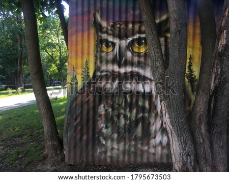 owl is painted on a fluted street wall