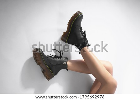 woman in black leather shoes from the new collection on a white background girl's legs in fashionable eco-leather shoes fall-winter 2020. macro photo                               #1795692976