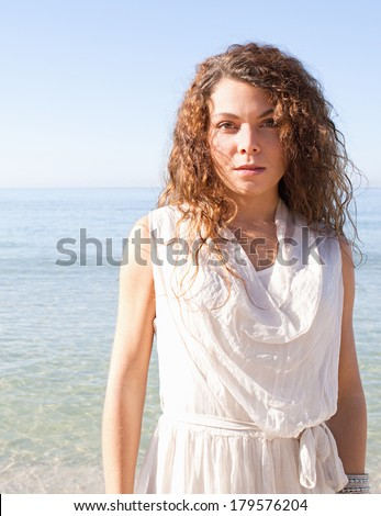 Portrait of a beautiful young woman standing and relaxing on a white sand beach with an intense blue sky on a summer holiday by the sea during a sunny day. Outdoors health and travel lifestyle. #179576204