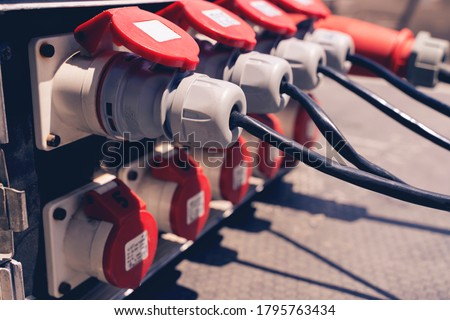 Plug in the power cord, many outlets with black plugs plugged in close up. Electricity in production. Royalty-Free Stock Photo #1795763434