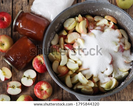 The process of making jam. We boil apple jam and close it in jars for future use. Wooden background with apple jam, apples, glass jars and a saucepan with chopped apples. #1795844320