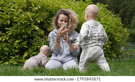 Young mom taking pictures of her baby twins with smartphone in the park