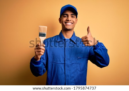 Young handsome african american painter man wearing uniform using painting brush happy with big smile doing ok sign, thumb up with fingers, excellent sign
