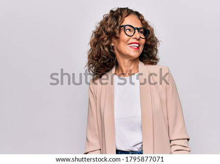 Middle age beautiful businesswoman wearing glasses standing over isolated white background looking to side, relax profile pose with natural face and confident smile. #1795877071