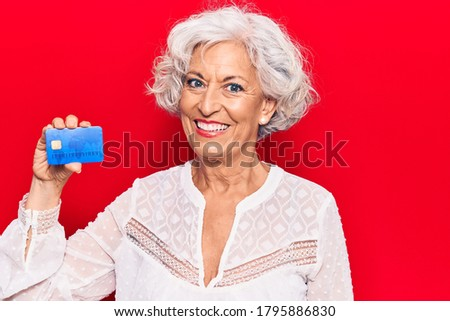 Senior grey-haired woman holding credit card looking positive and happy standing and smiling with a confident smile showing teeth