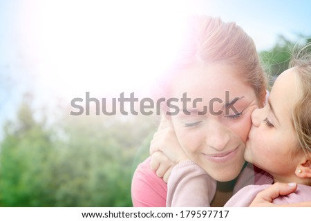 Portrait of little girl giving kiss to her mom