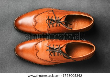 Pair of brown shoes on a black background. Men's fashion shoes. Classic men's shoes made of genuine leather. Men's accessories. Elegant stylish shoes #1796005342