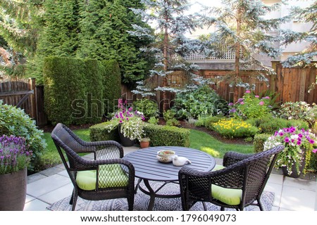 Beautifully landscaped small Canadian garden in summer. Blue spruces, hosta, astilbes and azaleas are just some of the many plants in this cozy little backyard.  Royalty-Free Stock Photo #1796049073