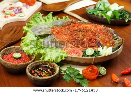 Fried fish sprinkled with hot chili sauce on a wooden table. Usually used for menu list pictures or food pictures in restaurants. Top view