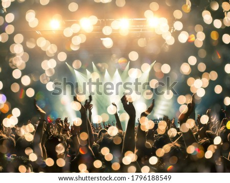 Image shot during a music festival. Light comes from a stage with a band show, people silhouettes are visible in front of it. Royalty-Free Stock Photo #1796188549