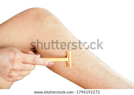 closeup woman hand shaving hairy leg by razor blade isolated on white background