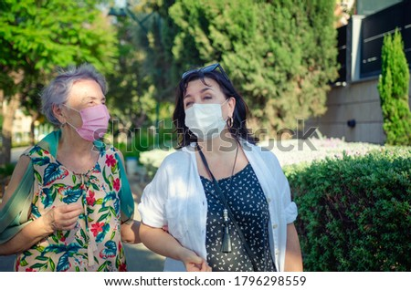 Caregiver or companion and senior adult woman speak in a friendly manner as they walk. Both are wearing protective face masks.  Royalty-Free Stock Photo #1796298559