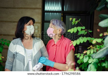 A volunteer or advanced physiotherapist walks a lonely old woman several times a week. As it should be in the Coronavirus epidemic, both put on protective face masks and gloves. #1796298586