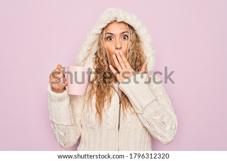 Young beautiful blonde woman wearing casual sweater with hood drinking cup of coffee covering mouth with hand, shocked and afraid for mistake. Surprised expression #1796312320