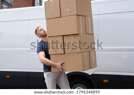 Movers Carrying Heavy Large Box Stack Near Truck Royalty-Free Stock Photo #1796348899
