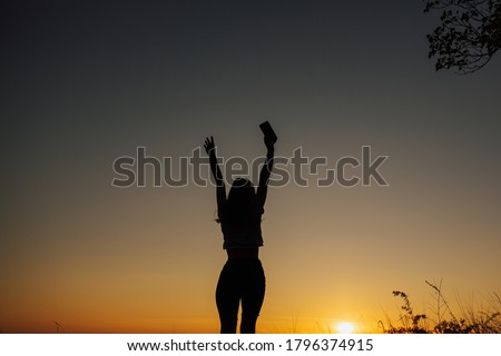 The girl at sunset. She stands back to the camera on the top of the mountain and looks at the sunset, welcomes the sun with her hands up. Girl listen the music.  Copy space. #1796374915