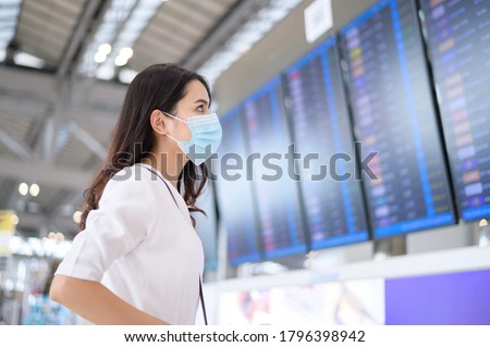 A traveller woman is wearing protective mask in International airport, travel under Covid-19 pandemic, safety travels, social distancing protocol, New normal travel concept . #1796398942