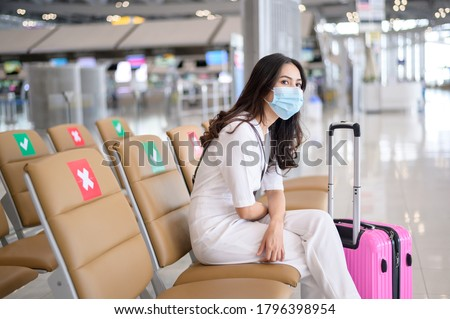 A traveller woman is wearing protective mask in International airport, travel under Covid-19 pandemic, safety travels, social distancing protocol, New normal travel concept . Royalty-Free Stock Photo #1796398954
