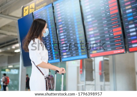 A traveller woman is wearing protective mask in International airport, travel under Covid-19 pandemic, safety travels, social distancing protocol, New normal travel concept . #1796398957