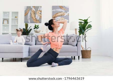 Young happy mother doing morning exercises in yoga pose while her little daughter watching cartoons at home.