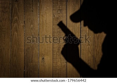 Shadows of a Men with a handgun on a natural grunge wood background, with space for text or image. You can see more on my page. #179656442