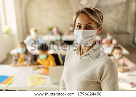 Female teacher wearing a face mask while teaching children at elementary school and looking at camera.  Royalty-Free Stock Photo #1796624458