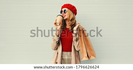 Autumn portrait of attractive young woman with shopping bag and coffee cup wearing red french beret over gray background #1796626624