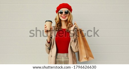 Autumn portrait of attractive young woman with shopping bag and coffee cup wearing red french beret over gray background #1796626630