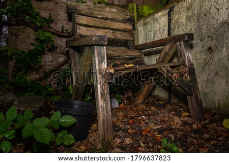 Decaying wooden garden chair abandoned in the forgotten corner of the garden #1796637823