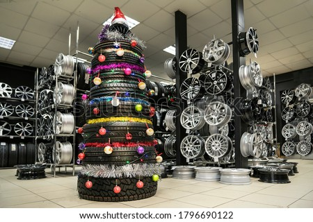 Christmas tree made of car tires and wheels, installed in a car shop selling spare parts, tires and alloy wheels. festive new year's illustration for car business and car tuning organizations. #1796690122