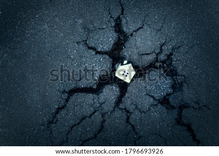 Destruction of residential buildings concept with the little toy house in a cracked asphalt hole. Royalty-Free Stock Photo #1796693926