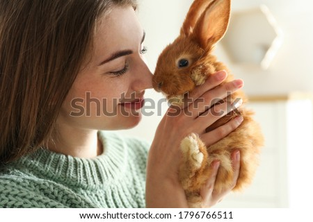 Young woman with adorable rabbit indoors, closeup. Lovely pet